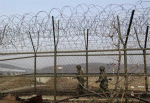 South Korean army soldiers patrol along a barbed-wire fence near the border village of Panmunjom.
