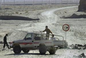 In this Oct. 7, 2001, file photo, Iranian border guards watch for Afghan refugees on a road which leads to Afghanistan.