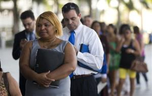 In this Jan. 15, 2013, photo, Racheel Weston, stood in line with a few hundred other job seekers, during the job fair that the Miami Marlins hosted at Marlins Park in Miami.