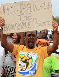 A man protests  outside the courthouse  against the granting of bail  for the eight police officers charged with murdering a taxi driver Mido Macia who was dragged from a police vehicle last week in Benoni outside Johannesburg, South Africa, Friday, March 8, 2013. The killing of Mido Macia, a taxi...