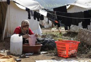 In this Tuesday, Feb. 19, 2013 photo, a Syrian refugee washes laundry outside her tent, at Atmeh refugee camp, in the northern Syrian province of Idlib.
