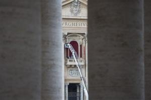 Workers use a crane to place a burgundy curtain around the doorframe of the balcony on the front of St. Peter's Basilica where the newly elected Pope will make his first appearance, March 11, 2013.