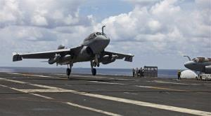 In this photo taken on Saturday, Aug. 13, 2011, a U.S. Navy jet EA-6B Prowler approaches to land on the deck of USS George Washington in the South China Sea.