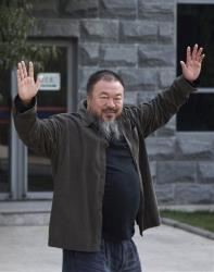 Chinese activist artist Ai Weiwei waves to the journalists before he enter the Beijing No. 2 People's Intermediate Court last fall.
