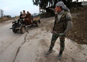 In this Thursday, Feb. 21, 2013 photo, a Free Syrian Army fighter, right, watches Syrian villagers passing a checkpoint at the Christian village of Yacobiyeh, Syria.