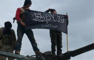 In this Friday, Jan. 11, 2013 photo provided by Edlib News Network, rebels from al-Qaeda affiliated Jabhat al-Nusra wave their brigade flag as they step on a Syrian air force helicopter that they captured in Idlib province, northern Syria.