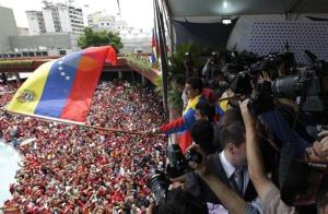 Venezuela's acting president Nicolas Maduro waves a Venezuelan flag over supporters after registering his candidacy for president Monday, March 11, 2013.