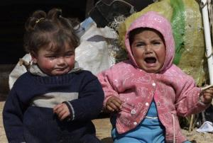 In this Tuesday, Feb. 19, 2013 photo, two Syrian refugee children sit outside their family tent, at Atmeh refugee camp, in the northern Syrian province of Idlib, Syria.