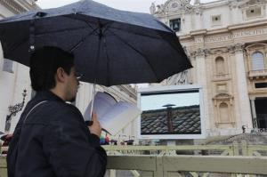 A visitor reads while waiting for smoke to emerge from the chimney on the Sistine Chapel during the second day of the conclave to elect a new pope in St. Peter's Square at the Vatican, Wednesday, March 13, 2013.