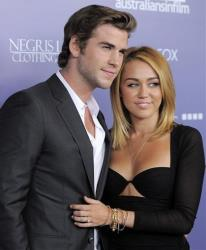 Actor Liam Hemsworth, left, an honoree at the Australians in Film 8th Annual Breakthrough Awards, poses with his fiance Miley Cyrus on Wednesday June 27, 2012, in Los Angeles.
