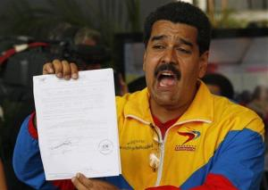 Venezuela's acting President Nicolas Maduro showing his certificate after registering his presidential candidacy in Caracas, Venezuela, Monday, March 11, 2013.