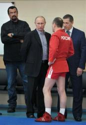 Russian President Vladimir Putin, center, and Steven Seagal, left, speak to an athlete as they visit a new sports arena in Moscow, Wednesday, March 13, 2013.