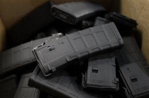 In this Feb. 28, 2013 photo, newly-assembled 30-round capacity ammunition magazines for high-velocity rifles are stacked awaiting packaging, inside the Magpul Industries plant, in Erie, Colo.