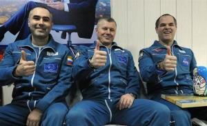 Russian cosmonauts Yevgeny Tarelkin, left, Oleg Novitsky, center, and NASA astronaut Kevin Ford pose for a photo at the airport of the Kazakh city of Kostanai.