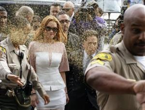 Actress Lindsay Lohan is showered with gold glitter, second left, as she arrives with her attorney Mark Heller, after attending a trial Monday, March 18, 2013, at Los Angeles Superior court.