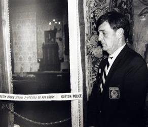 In this March 21, 1990 file photo, a security guard stands outside the Dutch Room of the Isabella Stewart Gardner Museum in Boston, where robbers stole more than a dozen works of art.