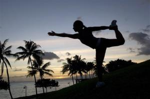 In this photo released by lululemon athletica, Angela Yamashita strikes a dancer's pose at the end of a sunset photo shoot in Kakaako Park, Honolulu, Sunday, Aug 19, 2007.