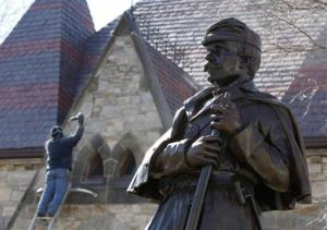In this March 25, 2011 photo, a workman does repairs at the Framingham History Center behind a statue of a Union soldier in Framingham, Mass.