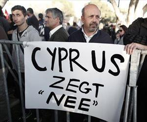 Protester stand in front of a banner which reads Cyprus Says No during a crucial parliamentary vote on a plan to seize a part of depositors' bank savings.