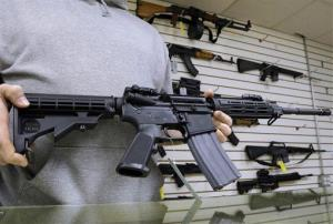 A gun shop owner shows off an AR-15 assault rifle.