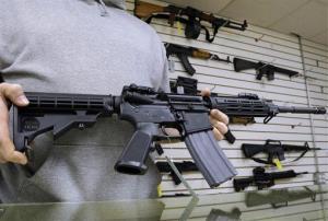 A gun shop owner shows off an AR-15 assault rifle.