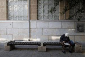 A woman solves a crossword as she sits on bench outside a Bank of Cyprus building in Nicosia, Cyprus, Wednesday, March 20, 2013.