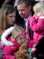 Alissa Parker, left, and her husband, Robbie Parker, center, carry their daughters Samantha, 3, and Madeline, 4, following funeral services for their daughter Emilie, on Saturday, Dec. 22, 2012.
