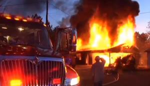 Fire consumes a woman's house after she set a snake on fire in her backyard.