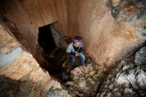A Syrian girl, leaves a cave used as shelter from Syrian government forces shelling and airstrikes, at Jabal al-Zaweya, in Idlib province, Syria, Thursday, Feb. 28, 2013.