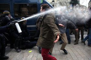 A protester clashes with riot police officers in Paris yesterday.