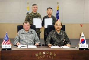 US Gen. James D. Thurman, seated left, and Chairman of South Korean Joint Chiefs of Staff Jung Seung-jo, seated right, pose for a photo after signing a military plan in Seoul, South Korea.