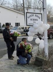 Volunteer firefighters place flowers at a makeshift memorial at a sign for the Sandy Hook Elementary school Saturday, Dec. 15, 2012 in the Sandy Hook village of Newtown, Conn.