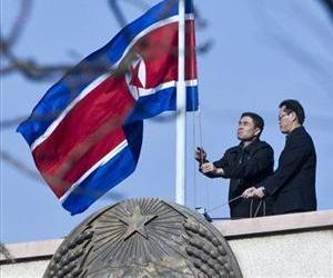 North Korean embassy staff members lower their national flag at half-mast to mourn the death of Kim Jong Il on the roof of the embassy in Beijing, China, Dec. 19, 2011.