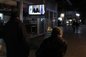 Cypriots watch a TV screen as President Nicos Anastasiades addresses the nation last night.