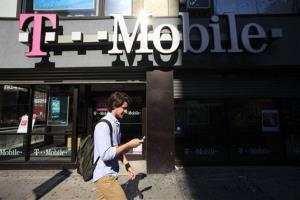 In this Wednesday, Sept. 12, 2012, file photo, a man using a cellphone passes a T-Mobile store.