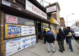 Crowds stand outside Eagles Liquors in Passaic, NJ Monday, March 25, 2013.