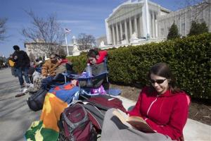 In this photo taken Saturday, March 23, 2013, Jessica Skrebes of Washington reads while waiting in line with others outside of the US Supreme Court in Washington in anticipation of Tuesday's Supreme Court hearing on California's Proposition 8.