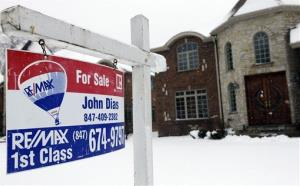 In this Wednesday, Feb. 27, 2013, photo, a for sale sign is seen outside a home in Glenview, Ill.