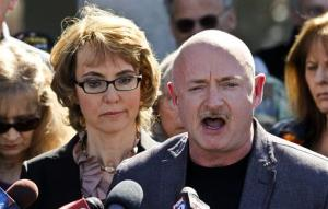 In this March 6, 2013 file photo, Gabrielle Giffords listens to her husband Mark Kelly during a return to the supermarket where she was wounded in a rampage two years ago in Tucson, Ariz.