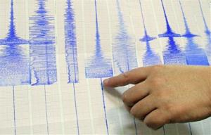 The seismology director at Taiwan's Central Weather Bureau points to Richter scale graphs.