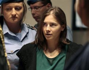 Amanda Knox is escorted as she arrives for an appeal hearing at the Perugia court, central Italy, Monday, Oct. 3, 2011.