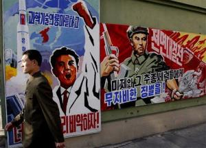 A North Korean man walks past propaganda posters in Pyongyang today.
