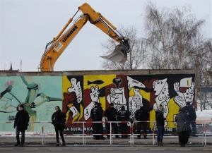 Police officers guard a construction site and sections of the East Side Gallery, while parts of the former Berlin Wall are removed in Berlin, Germany, Wednesday March 27, 2013.