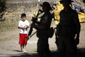 A boy looks on as policemen stand guard during a raid in Coban, Guatemala, Tuesday Dec. 21, 2010.