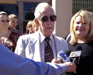 George Sanders, center, is joined by his attorney Janey Henze Cook, right, outside a Phoenix courtroom Friday.