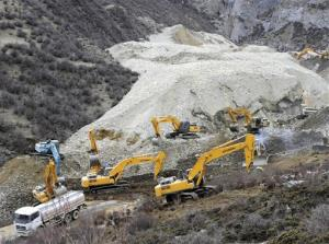 In this photo released by China's Xinhua News Agency, earthmovers remove rocks and mud at the scene.