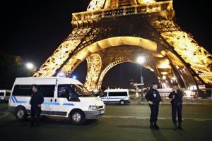 Police officers stand in front of the Eiffel Tower, in Paris, Tuesday Sept. 14, 2010.