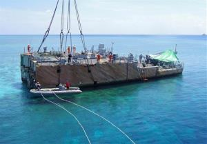 In this March 29, 2013 photo, workers prepare to lift part of the dismantled hull of the USS Guardian on the Tubbataha Reef.
