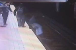 In this image taken from security video, Christopher Knafelc jumps off a subway platform in Philadelphia to help a man who fell onto the tracks Thursday, March 28, 2013.