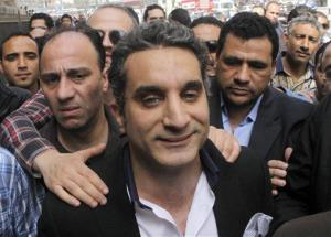 A bodyguard secures popular Egyptian television satirist Bassem Youssef in Cairo, Egypt, Sunday, March 31, 2013.